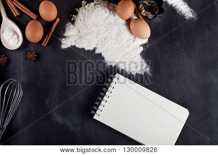 Ingredients like eggs flour cinnamon anise rolling pin paper on blackboard