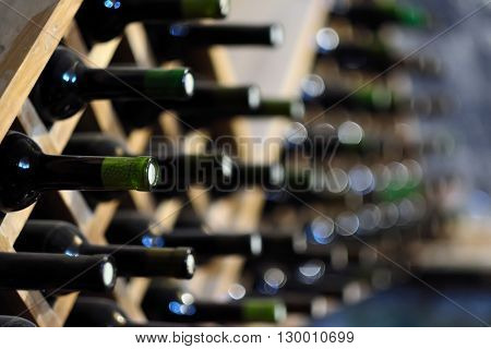 Resting wine bottles stacked on wooden racks in cellar