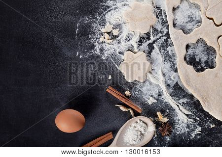 Cookie ingredients like eggs flour cinnamon anise rolling pin paper on blackboard from the top