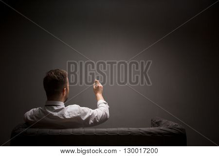 Businessman holding ballpen in front of him while sitting on comfortable sofa in studio. Back view of young man writing something.