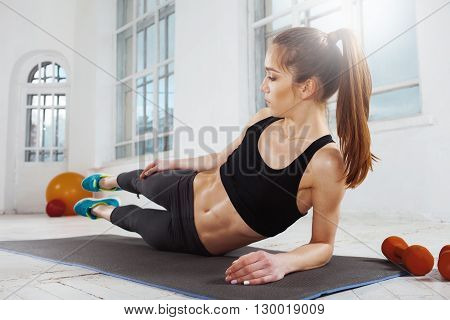 Beautiful young slim woman  doing push ups at the gym with orange dumbbells