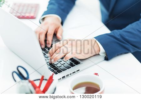 The hands of man on the keyboard of laptop computer