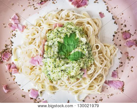 Tasty italian spaghetti with broccoli sauce ham and parsley on the pink plate. International cuisine. Food theme. One portion.