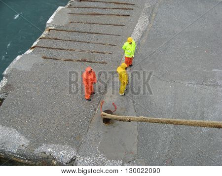 ISLAND OF ANDROS, CYCLADES, GREECE - SEPTEMBER 12, 2009: Three dock workers in wet work protective suit standing on the dock waiting for permission to release ship mooring ropes