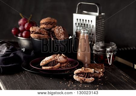 Italian maroni cookies on the plate and bowl with grapes chocolate milkshakes cloth notebook on dark old wooden background