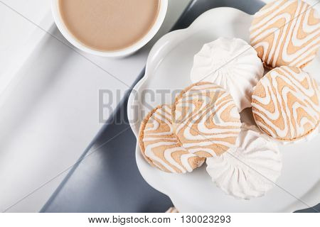 Cookies on gray plate with cup of coffee on white background top view