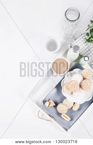 Cookies on white and gray plate with cups of coffee and bottles of milk on white shutters background with green and white flower top view
