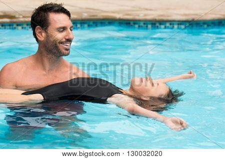 Little girl learning how to swim with swimming instructor. Happy smiling father and daughter relaxing in a swimming pool in a resort. Relaxed child floating in swimming pool with her dad.