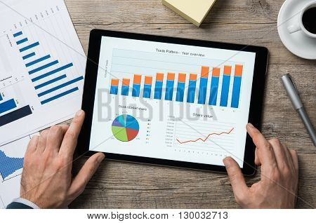 Top view of digital tablet with financial year overview on screen. Businessman analyzing investment charts with digital tablet on wooden desk at office. positive stock market trend.