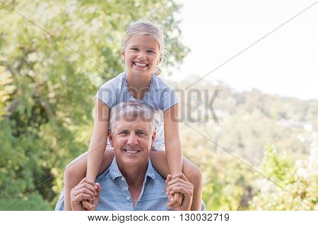 Grandfather giving granddaughter ride on shoulder in the park. Smiling granddaughter on grandpa shoulder. Portrait of healthy grandfather playing with granddaughter and looking at camera.