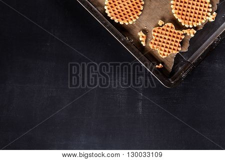Waffles on baking paper on blackboard from the top
