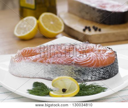 Salmon steak with lemon and olive oil on the white plate