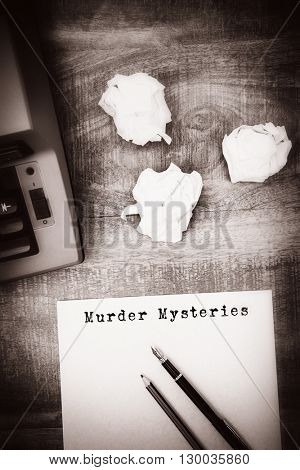 Murder mysteries message on a white background against view of an old typewriter and paper