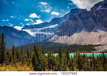 The Glacier Crowfoot over Bow River  in environment of bright striped mountains. Canada, Rocky Mountains, Banff National Park