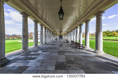 Colonnade into indefinite with benches in a park