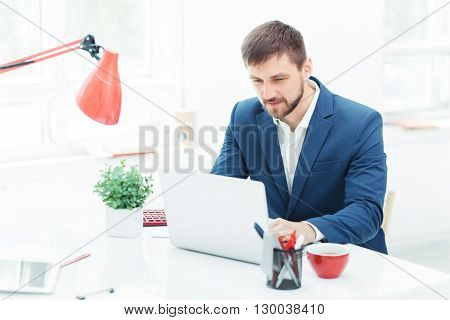 Elegant successful  businessman sitting at the office and looking throw the information on his laptop