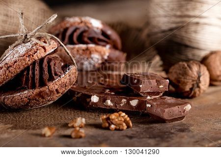 Italian maroni cookies with pieces of chocolate and walnuts on old wooden background