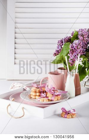 Cookies with pink ribbons on a white plate and tray with cloth pink mugs chocolate milkshakes and vase with lilac flowers on white shutters
