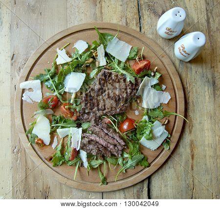 Brazilian beef steak with arugula, parmesan and cherry tomatoes