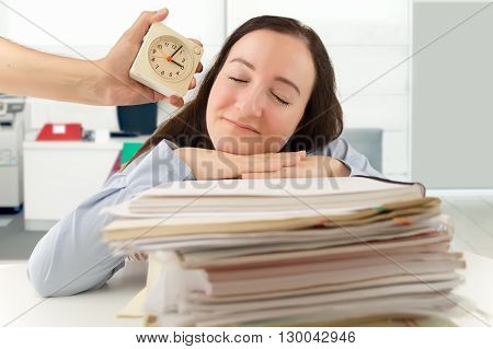 businessman with an alarm clock that wakes a business woman sleeping at the office