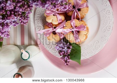 Cookies with pink ribbons on a white plate with lilac flowers and chocolate milkshake