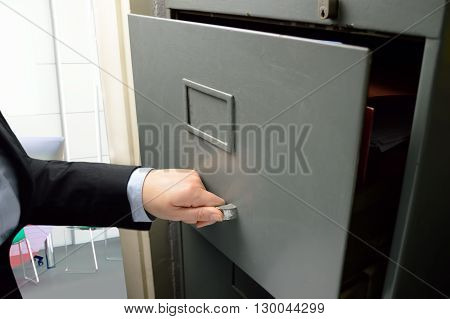 Business woman opening an old file cabinet in the office