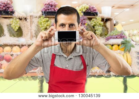 shopman holding a mobile phone against her mouth at the greengrocery