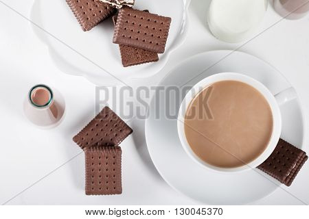 Cup of coffee and few bottles of milk and chocolate milkshakes on white background from the top