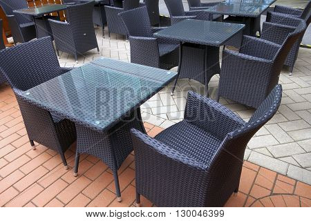 Tables and chairs in empty street cafe in early spring waiting for opening the summer season.