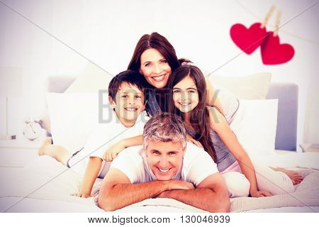 Happy familly looking at the camera against hearts hanging on a line