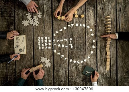 Top view of six business partners working on a project together by brainstorming ideas using puzzle pieces wooden pegs and cubes and taking notes.