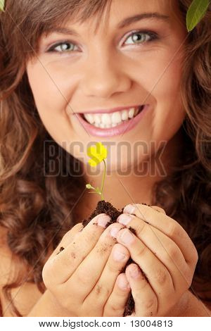Closeup portrait of a beautiful happy young woman holding flower