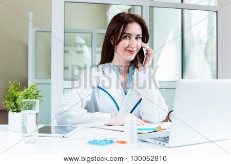 Young pretty woman doctor sitting at the table with laptop