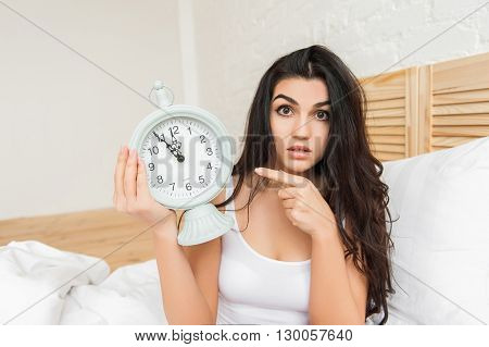 Young woman with alarmclock on the bed on pointing on it