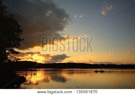 Two Men Canoeing at Sunset on a Wilderness Lake