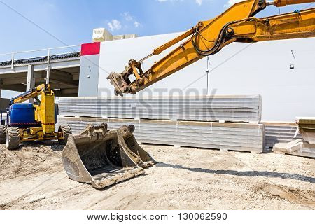 Excavator is replacing tool for bucket at construction site.
