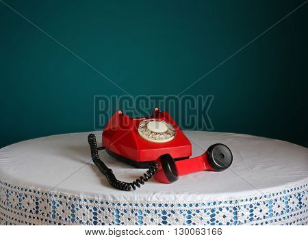 Red retro rotary phone off the handset at a round table with a white tablecloth with lace on a blue background. Retro still life.
