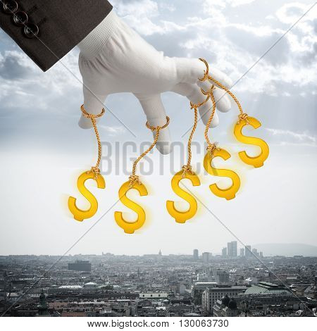 Dollar signs hanging on strings like marionette. Conceptual photography