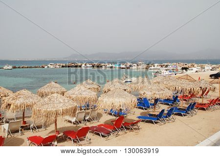 AGISTRI, GREECE - MAY 12, 2016: The sandy beach at Skala on the Greek island of Agistri. The 5.5km long island is under one hour from the Athens port of Piraeus. Aegina island is in the distance.