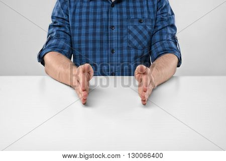 Close-up hands of man showing small size of something. Symbols and gestures. Imitation. Concept. Body language. Cropped portrait. Hand gesture.