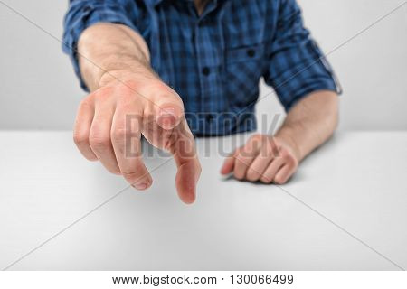 Close-up hands of man pointing at the viewer. Index finger pointing at you. Cropped portrait. Symbols and gestures. Concept. Body language. Hand gesture. Specify and select.