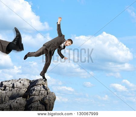 Businessman kicked by his boss big foot from rock