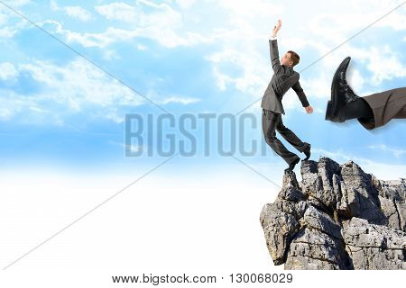 Businessman kicked by his boss big foot from edge of mountain