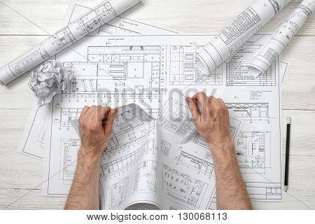 Close-up hands of architect tearing a bad architect drawing. Anger sign. Worry process. Nervous condition. Workplace of architect or constructor. Engineering work. Construction and architecture. Architect drawing. Draft.