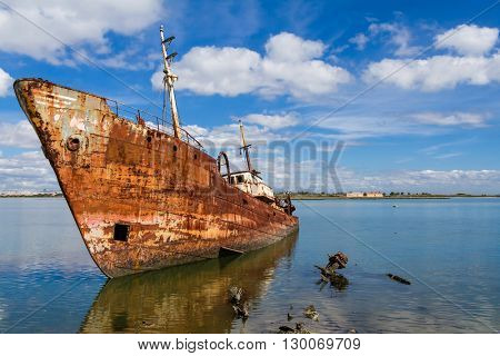 Old ship run aground and rusting in the shore. Seixal, Portugal.