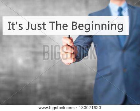 It's Just The Beginning - Businessman Hand Holding Sign