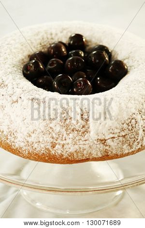 Postre: torta de vainilla con cerezas sobre mesa