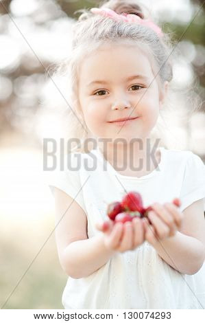 Smiling baby girl 3-4 year old holding strawberries outdoors closeup. Looking at camera. Childhood. Healthy eating.