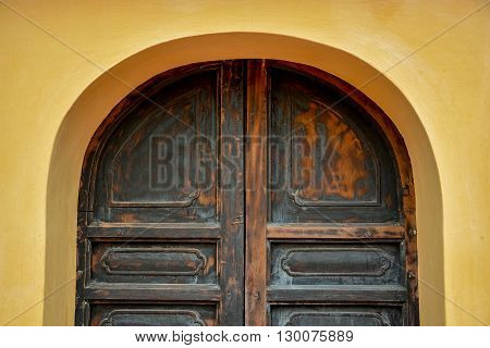 Old grunge arch wooden door on yellow plaster texture wall - can use for background in architecture or urban concept