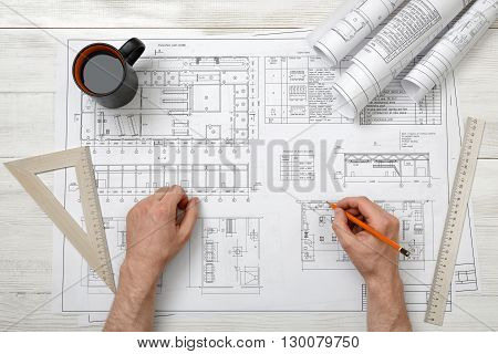 Close-up hands of architect working with pencil on a drawing. Workplace of architect. Engineering work. Construction and architecture. Architect drawing. Non-stop work.